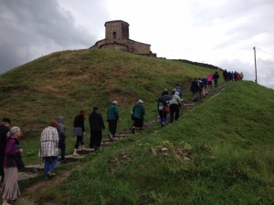 pilgrims walking up a hill to a church in Serbia